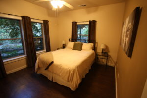 queen bed in Blacktail Deer bedroom with windows and ceiling fan